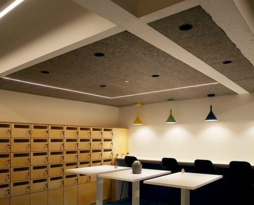 Playful acoustic ceiling panels with round holes and colorful lamps