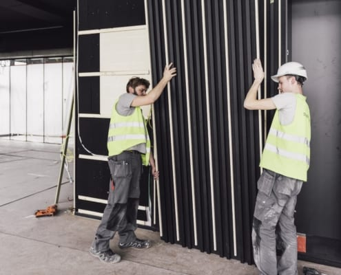 Installation of a black PETAC © wall set with wooden slats
